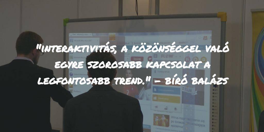 Interaktív digitális tábla előtt áll két öltönyös férfi, s néznek valamit a kijelzőn